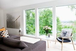 Sofa, bouquet on table and retro chair in front of floor-to-ceiling window with view of town