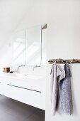 Towels hanging on rustic rack with hooks next to white washstand with wall-mounted fittings below mirrored cabinet