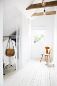 Dressing room with translucent curtain and wooden chair in front of window in attic room