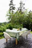 Shell chairs with metal frames around table with tablecloth on wooden terrace in front of woodland landscape