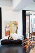 Gemütliche Loftatmosphäre - moderne Malerei hinter Kissensammlung auf ledernen Sitzkissen