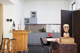 Bambus-Bar, Esstisch mit Designerstühlen und Ethnofigur vor schlicht moderner Küchenzeile in Vintage-Loft