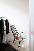 Sparsam möblierter Schlafraum mit Vintage Armlehnstuhl im Shakerstil, 70er Jahre Flokati und Kleiderständer auf Rollen