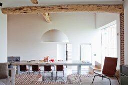 Blick durch breiten Durchgang auf Esstisch mit Stühlen in minimalistischem Wohnzimmer und Boden teilweise aus Ziegelsteinen