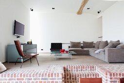 Blick auf Empore mit gemütlicher Couchecke und Sideboard in minimalistischem Loungebereich