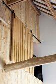 Blick nach oben auf Holzwand mit schiebbarem Holzelement vor Galerie mit Geländer unter Dachstuhl