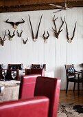 Tische mit roten gepolsterten Stühlen und Holzstühlen vor weisser Holzwand mit Tierhörnern in einem Restaurants