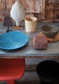Kunsthandwerkliche Objekte auf Tisch, darunter eingeschobene Hocker