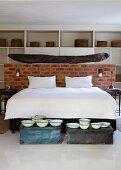 Doppelbett mit weisser Bettwäsche vor halbhoher Ziegelwand und Vintage Schüsseln auf Truhen am Bettende im Schlafzimmer