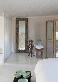 Vintage Schüsseln am Bettende auf Truhe und raumhoher Spiegel mit Rahmen an Wand lehnend neben Badewanne im Badbereich