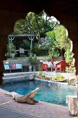 Blick durch geschnitzten Holz Rundbogen auf Pool mit Krokodil-Figur am Poolrand