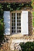 Sprossenfenster mit weissen Holzläden in berankter Natursteinfassade
