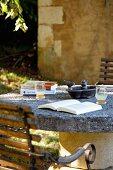 Buch auf Tisch mit Natursteinplatte auf der Terrasse