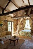 Rustikaler Wohnraum mit Sofa und Beistelltisch vor Schlafecke neben Treppe zur Galerie