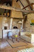 Beistelltisch und Sofa vor Holzbackofen und Natursteinwand in rustikalem Wohnraum