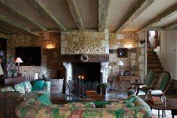 Geblümte Sofagarnitur und Couchtisch vor offenem Kamin in rustikalem Wohnzimmer mit Holzbalkendecke