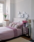 Double bed with pale pink bedspread, silver bedside table and white chest of drawers in elegant bedroom