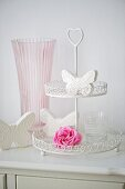 Glass of water, pink rose and butterfly ornaments on cake stand