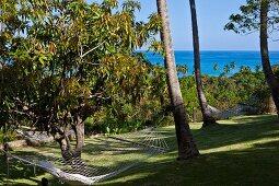 Blick über aufgehängte Hängematten und Grünfläche zum blauen Meer