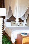 Doppelbett unter weißem Baldachin vor dunkler Holzwand und grünem Bettvorleger