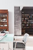 Modern, designer dining area with old dresser; bookcase with letter ornaments in background