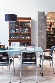 Modern chairs with latticed seats and backrests, glass table on castors and designer lamp in front of antique display case and bookcase in background