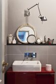 Washstand with countertop trough on red base unit below designer wall lamp and collection of round mirrors