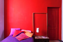 Simply furnished bedroom in seductive shades of red and purple
