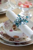 Festive place setting with floral crockery and linen napkin in beaded napkin ring