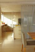 Dining area in front of an open kitchen with center block and transparent curtain as a screen