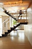 Modern metal staircase with light wood flooring in the open living room