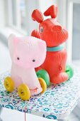 Plastic, pull-along dog and cat-shaped toys on wheels
