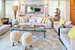 Fellhocker, Treibholzkunst und Riesenmuscheln als Deko in einladendem Sitzbereich mit Sofagruppe