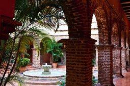 Blick vom Säulengang auf plätschernden Brunnen