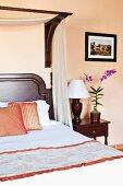 Rosafarbenes Schlafzimmer mit Edelholzbett und Nachttischlampe mit Holzfuss