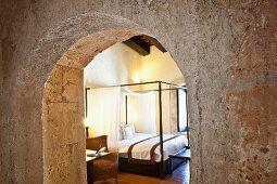 Blick in helles Schlafzimmer mit imposantem Doppelbett und Korbstuhl