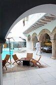 Blick durch Rundbogen auf Pool und Outdoor-Möbel in orientalischem Innenhof eines Hotels