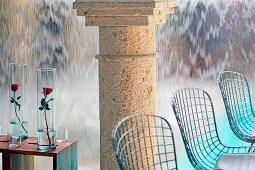 Stühle aus Drahtgestell und Rosen in Glasvasen auf Beistelltische vor Steinsäule und wasserfallartiger Wand