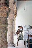 Gedeckte Tische im Arkadenbereich mit mächtigen Steinsäulen im Innenhof