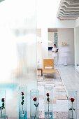 Glasvasen mit roter Rose auf Boden eines Innenhofs und Blick auf Personal vor Spa-Bereich