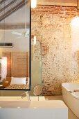 Designer Badezimmereinrichtung vor rustikaler Ziegelwand und Blick in Spiegel auf Bett