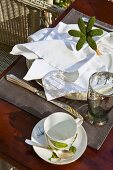 Breakfast place setting with flower ornament and white linen napkin on wooden table