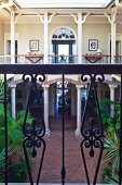 View into elegant hotel courtyard with colonnade from balcony with wrought iron balustrade