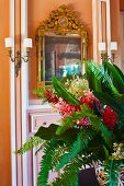 Tropical bouquet on table in front of apricot wall with gilt-framed mirror flanked by sconce lamps