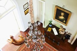 View down into grand foyer - chandelier above Oriental rug and antique console table below oil painting