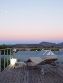 Twilight atmosphere on roof terrace with view of mountain landscape - dog on wooden floor next to sun lounger