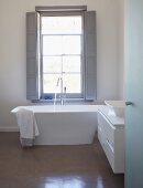 View through open door into designer bathroom with free-standing bathtub below window
