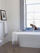 Modern bathroom with free-standing bathtub below window and cat sitting on windowsill