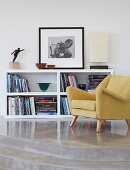 50s armchair in front of half-height shelving unit on concrete platform with steps