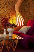 Gestreifte Designer-Lampe, Sessel und Glastisch in Wohnzimmerecke